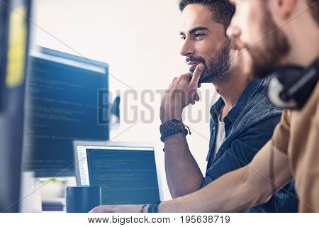 Low angle side view males expressing thoughtfulness while working on computer in room together