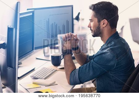 Side view orderly man having job on digital device. He looking at screen while sitting at table in office