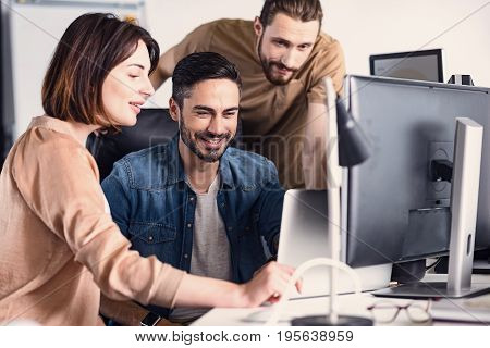 Smiling man discussing with outgoing girl and cheerful comrade during work in office. They are looking at laptop with joy