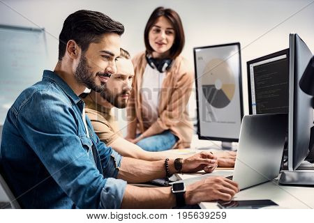 Side view smiling bearded male worker showing data on laptop to colleagues while sitting at table in modern apartment