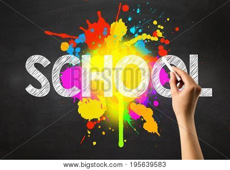 Female hand holding white chalk in front of a blackboard with school written on it and a colorful splash in the background