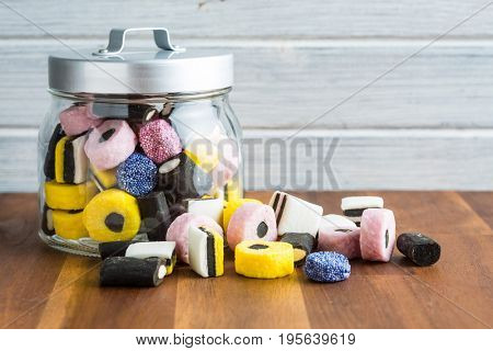 Mixed liquorice candies on wooden table.