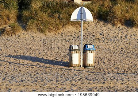 Two garbage bin for recycling on sand at the beach