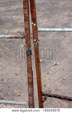 Metallic padlock and chain lock at fence door.