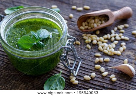 Pesto genovese - traditional Italian green basil sauce with pine nuts basil and garlic on rustic wooden background.
