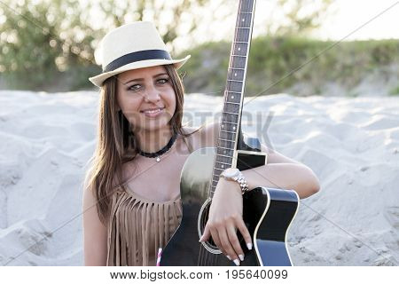 Beautiful Young Woman With A Hat And Guitar A Cowboy-style  On A Sandy Beach