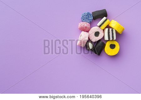 Mixed liquorice candies on colorful background. Top view.