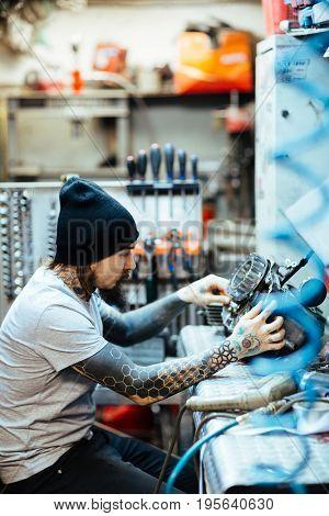 Side view portrait of modern tattooed man fixing broken car parts in  workshop