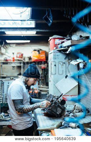 Side view portrait of modern tattooed man fixing broken engine  in  workshop