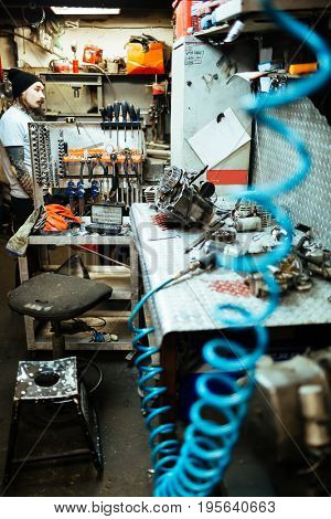Mechanics table with equipment, tools and car parts for repair in workshop