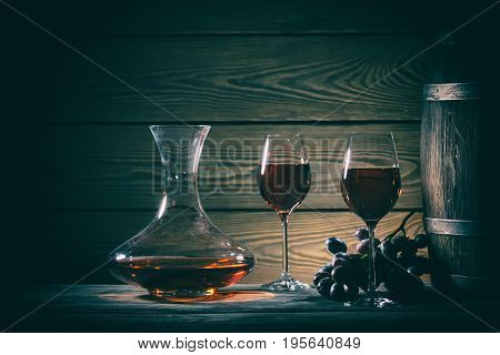 Decanter, two glasses of red wine and barrel on a wooden table. Toning.