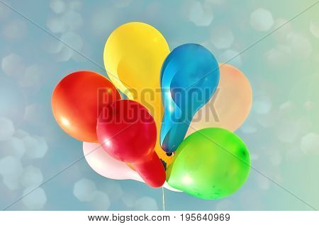 Multicolored balloons against the sky with bright sun vintage toning