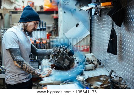 Side view portrait of modern tattooed man inspecting broken engine at table in motorcycle workshop