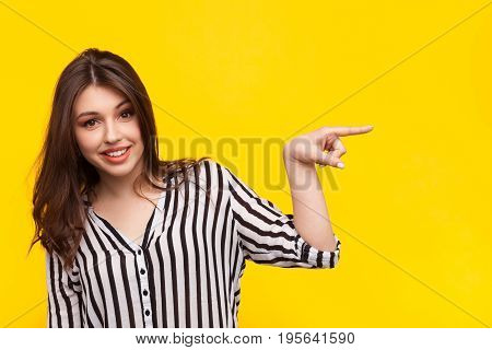 Young girl in striped shirt pointing away and smiling at camera on yellow background.