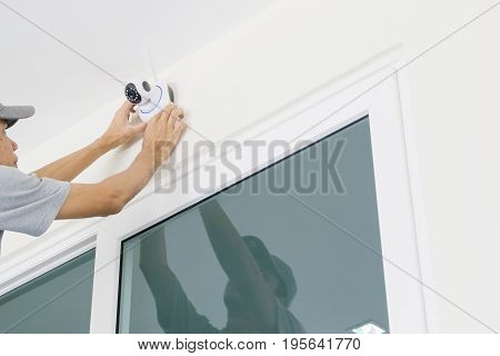 Technicians are installing a wireless cctv camera on the wall can connect to the Internet and control the camera via a smartphone or tablet.
