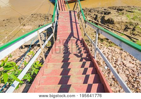 Up view of the wodeen stairs tha lead to the Madeira river. Red white and green stairs on river bank.