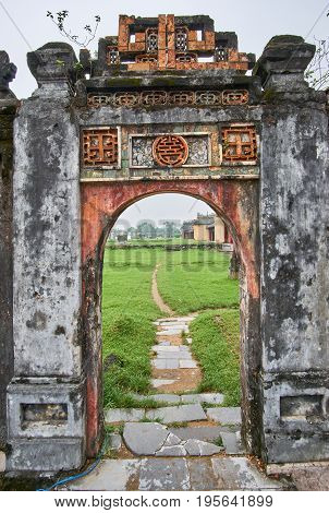 Traditional vietnamese entrance door in the imperial city, Hue, Vietnam, on a foggy day