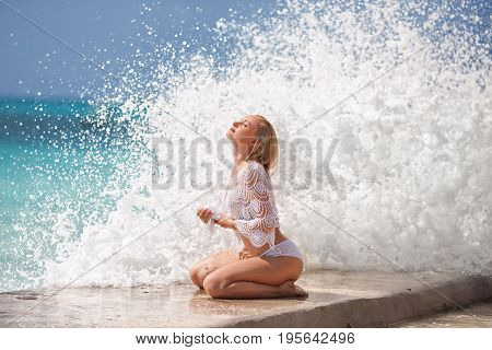 Beautiful blonde woman in the knitted white swimsuit sitting on the lonely pier with huge ocean waves. Zanzibar. Nungwi.