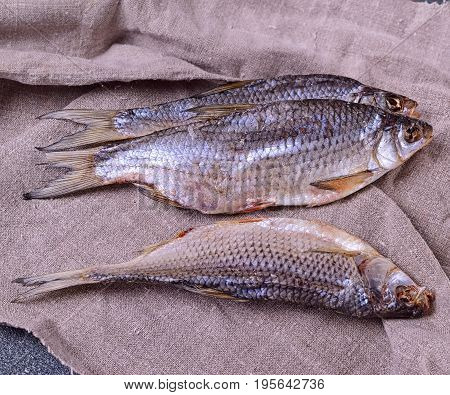 Dried river fish ram on a gray napkin top view