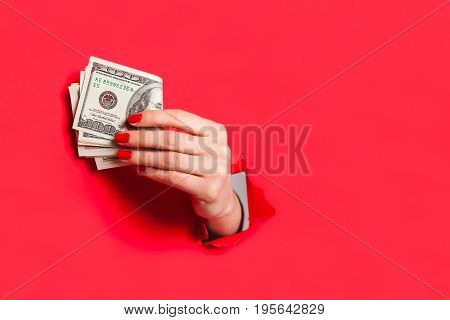 Crop female hand with manicure sticking out of hole in red paper holding dollar bills.