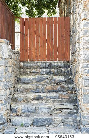 Entrance to the backyard, wooden plank gate, stone stairs and wall