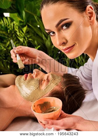 Mud facial mask of man in spa salon. Massage with clay full face. Girl on with therapy room. Man lying spa bed. Beautician with bowl therapeutic procedure green plant background.