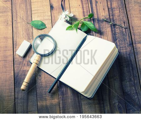 Photo of blank opened notebook and stationery: magnifier pencil and eraser on wooden background. Template for placing your design.