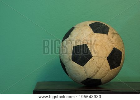 An old soccer ball on wooden table with retro green paint wall.