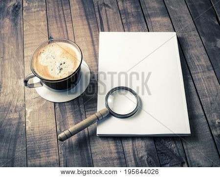 Photo of blank closed booklet magnifier and coffee cup on wood background. Responsive design mockup.