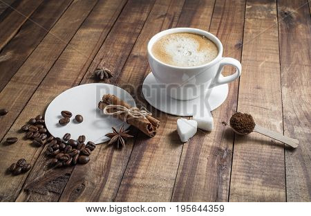 Photo of fresh tasty coffee on wood background. Coffee with spices. Coffee cup with cinnamon sticks coffee beans anise sugar and coasters. Top view.