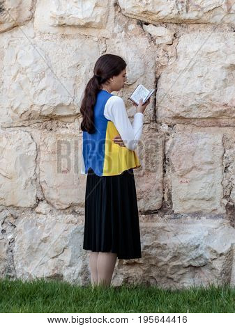 Jerusalem Israel July 14 2017 : Religious Jewish young woman reads book with prayers outside the fortress walls of the old city of Jerusalem Israel
