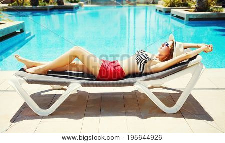 Summer Holidays - Beautiful Woman Lying On A Deckchair Over A Blue Water Pool Background
