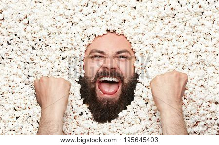 From above shot of bearded man all covered with popcorn and gesturing as winner.