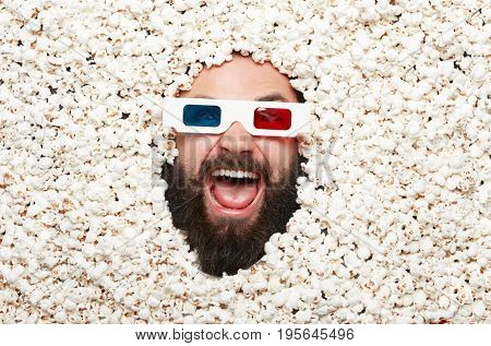 From above shot of man wearing stereo glasses and lying in popcorn.
