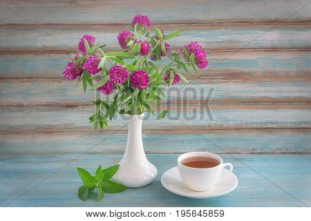 A bouquet of flowers and clover tea Cup in white ceramic bowl on a blue background. Studio photography. Pattern, plenty of space for text.