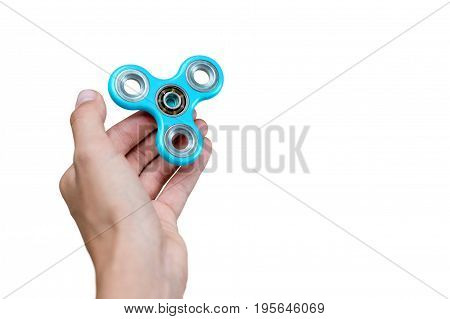 Fidget spinner. Blue hand spinner, fidgeting hand toy rotating on child's hand. Stress relief. Anti stress and relaxation adhd attention fad boy concept. Free space for text