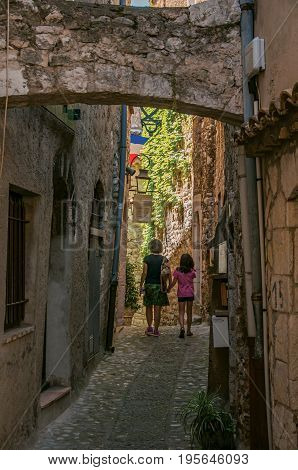 Saint-Paul-de-Vence, France - July 13, 2016. Mother and little girl in alley of stones in Saint-Paul-de-Vence, stunning medieval town completely preserved. In Provence region, southeastern France