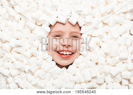 From above shot of child face in white marshmallows smiling at camera.