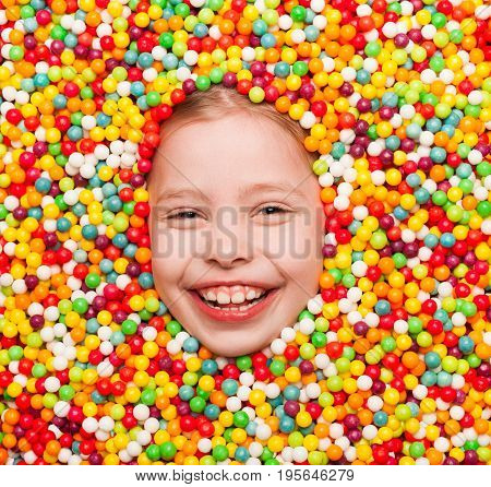 From above shot of cheerful child all covered with candies smiling at camera.