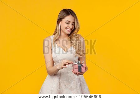Young lovely woman in white dress smiling while opening small giftbox on yellow background.
