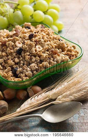 Healthy Granola Muesli Breakfast With Grape, Nuts And Wheat Ears In Green Glass Bowl