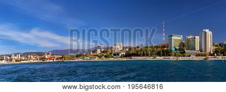 View from water at architecture of modern resort town Sochi hotels sanatoriums television tower and Sochi sea port with luxury yachts moored at pier. Krasnodarskiy kray Russia