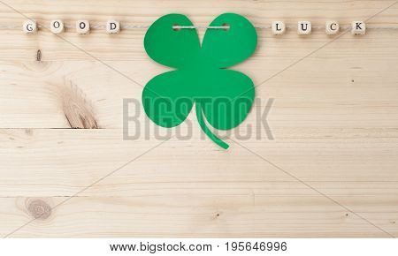 The words Good Luck and a cloverleaf on a cord on wood