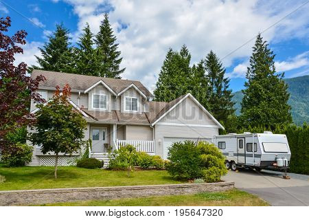 Big residential house with RV trailer parked on driveway. Family house on country side in British Columbia Canada