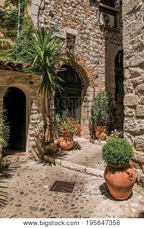 Alley with stone walls, doors and plants in Saint-Paul-de-Vence, a lovely well preserved medieval hamlet near Nice. Located in Alpes-Maritimes department, Provence region, southeastern France