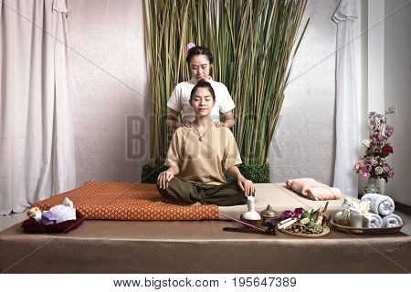 Thai Masseuse doing massage for woman in spa salon. Asian beautiful woman getting thai herbal massage compress massage in spa.She is very relaxed. Healthy Concept