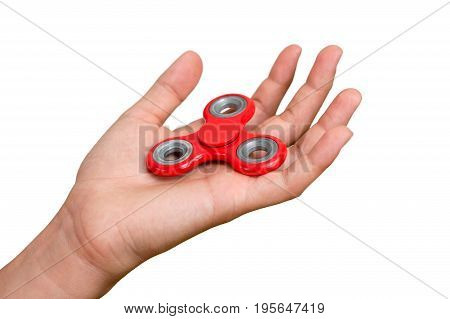 Red hand spinner. Boy playing a popular toy fidget spinner in his hand. Stress relief. Anti stress and relaxation adhd attention fad boy concept