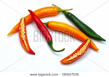Close up sliced red green and orange chilli pepper isolated on white background.