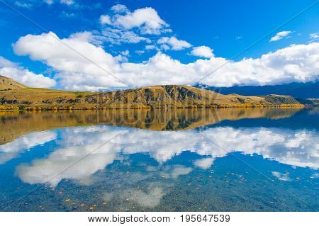 Autumn leaves in sunny day at reflection Lake Hayes South Island New Zealand