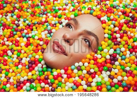 Young woman with dreamy glance looking out of colourful sweet candy drops.